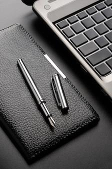 Ainda vida empresarial: laptop, porta-cartões, caneta-tinteiro.