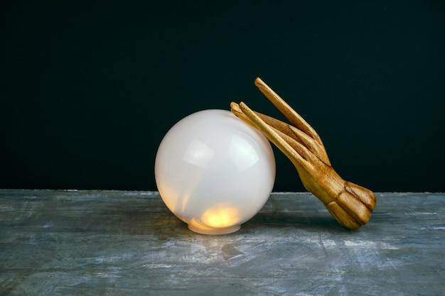 Ainda vida esotérica criativa com uma bola de previsões e duas mãos femininas de madeira