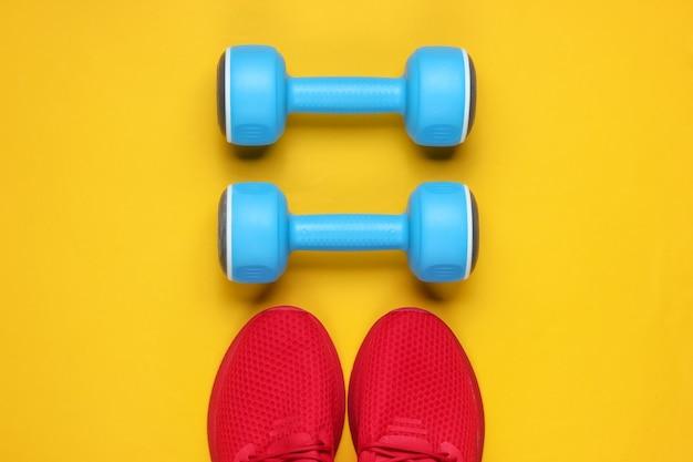Ainda vida esportiva minimalista. roupa esportiva. sapatos esportivos vermelhos para treinamento e halteres de plástico azul sobre fundo amarelo.
