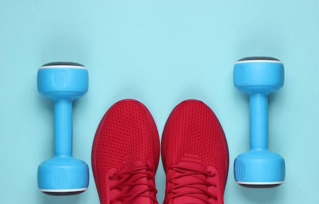 Ainda vida esportiva minimalista. roupa esportiva. sapatos esportivos vermelhos para treinamento e halteres em fundo azul pastel.