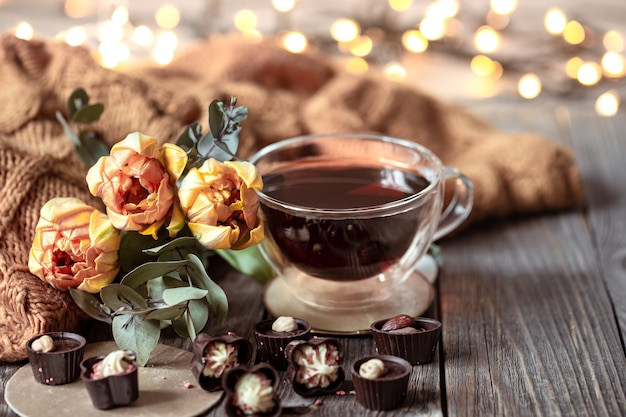 Ainda vida festiva com uma bebida em um copo, chocolates e flores em um fundo desfocado com bokeh.