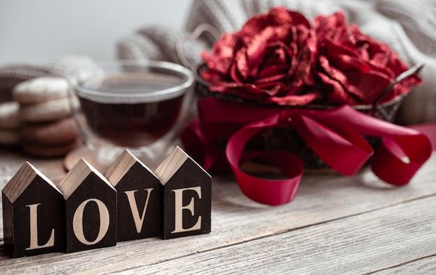 Ainda vida festiva em casa com a palavra de madeira amor, uma xícara de chá e flores