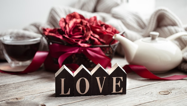 Ainda vida festiva em casa com a palavra de madeira amor, uma xícara de chá e um bule de chá