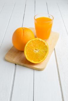 Ainda vida fruta laranja fresca, suco de laranja na mesa de madeira branca vintage