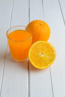 Ainda vida frutas frescas de laranja, suco de laranja na mesa de madeira branca vintage