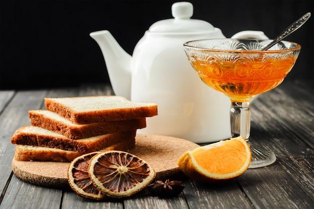 Ainda vida geléia de laranja em frasco de vidro, torradas e chaleira branca