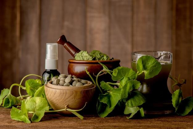 Ainda vida gotu kola verde deixa suco e spray sobre uma velha mesa de madeira.
