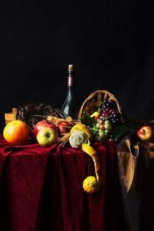 Ainda vida holandesa clássica com garrafa de vinho empoeirada e frutas em um escuro, vertical.