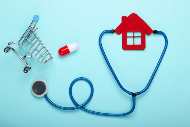 Ainda vida médica. estetoscópio, estatueta da casa do hospital, carrinho de compras com a pílula sobre fundo azul. postura plana