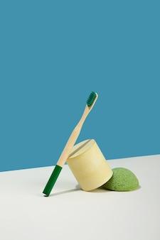 Ainda vida moderna. projeção diagonal isométrica. formas geométricas amarelas, suporte. escova de dentes de bambu. esponja konjac. resíduos zero, fundo azul e rosa pastel. estilo de vida ecológico e sustentável