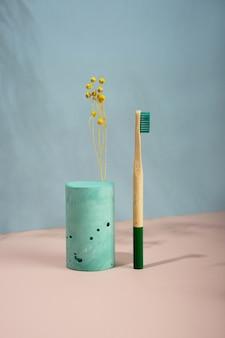 Ainda vida moderna. projeção diagonal isométrica. formas geométricas verdes, suportes e pódios. flores amarelas secas. resíduos zero, fundo azul pastel e rosa. estilo de vida ecológico e sustentável.