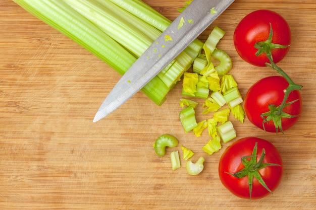 Aipo e tomate em uma placa de corte