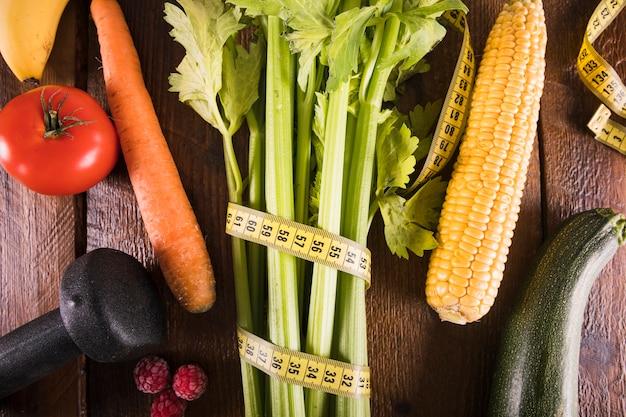Aipo envolto com fita métrica perto de legumes e halteres