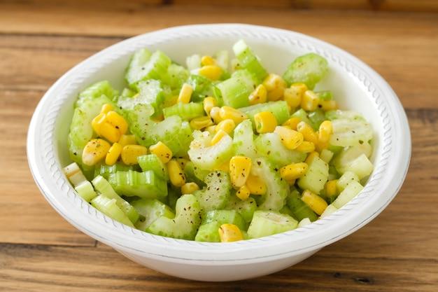 Aipo salada com milho em tigela branca em brown