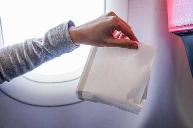 Airsick náuseas segurando o saco de vômito de doença de ar preparado para vomitar