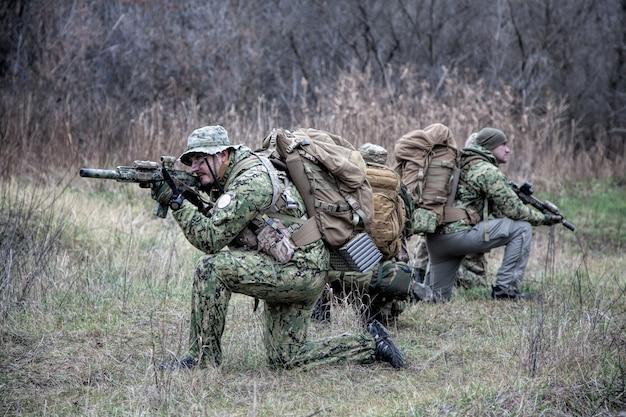 Airsoft, time de jogadores de strikeball, grupo de comando movendo-se cautelosamente na área da floresta, ajoelhando-se e olhando ao redor, cobrindo camaradas, controlando setores. comandante mostrando sinal de parada ou parada
