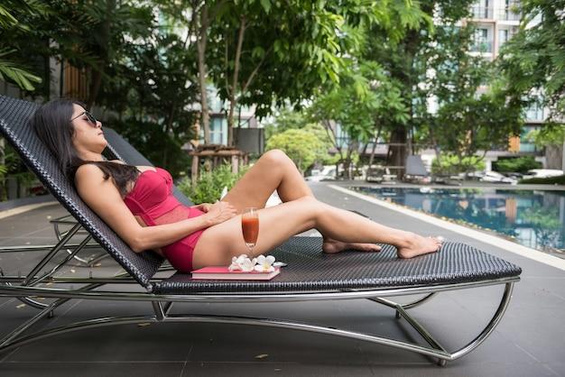 Aisan garota dormir na cadeira da piscina para se bronzear