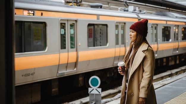 Aisan jovem mulher esperando trem na plataforma