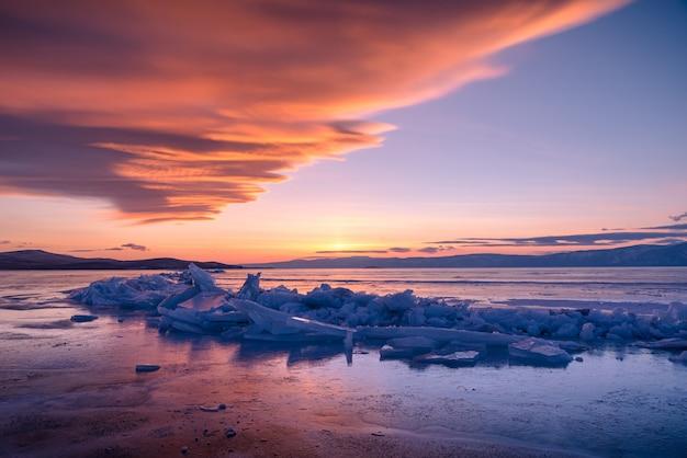 Ajardine a imagem do gelo de quebra natural sobre a água congelada no por do sol dramático no lago baikal, sibéria, rússia.