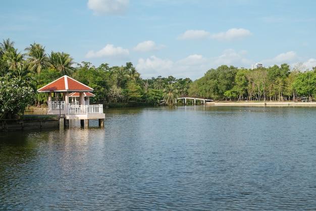 Ajardine a vista de um lago e pavilhões da margem com floresta.