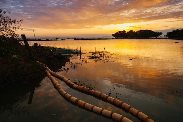 Ajardine a vista do lago nong han com por do sol e da cena crepuscular em sakon nakhon, tailândia.