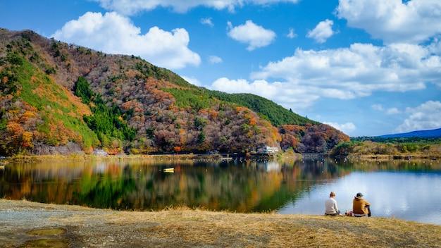 Ajardine a vista folhas de outono do lago kawaguchiko e casal sentado junto ao rio no japão