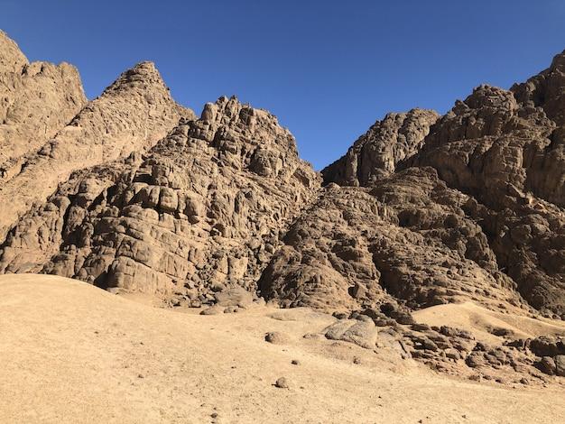 Ajardine montanhas de sandy, céu azul no deserto do egito.