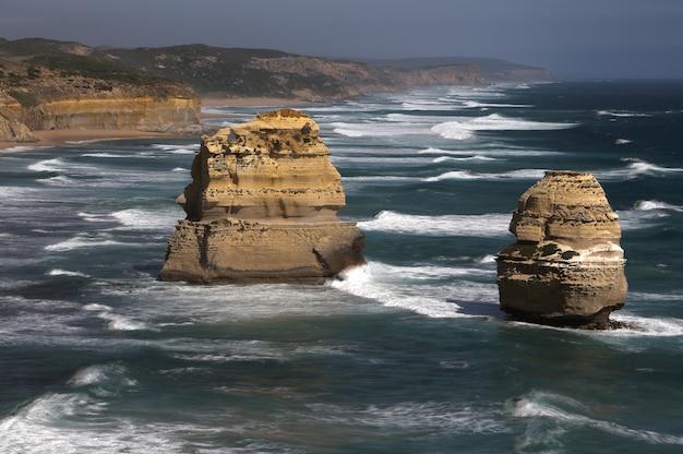 Ajardine o tiro das rochas em um corpo de água perto da costa.