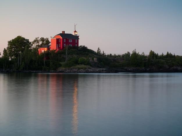 Ajardine o tiro de um lago calmo com uma casa vermelha na costa