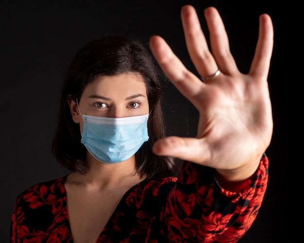 Ajuda a parar a infecção global por coronavírus. mulher com as mãos levantadas e máscara, espaço em preto