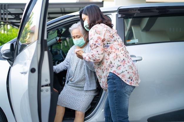 Ajuda e apoio paciente idoso asiático ou idosa senhora sentada em uma cadeira de rodas para se preparar para chegar ao carro