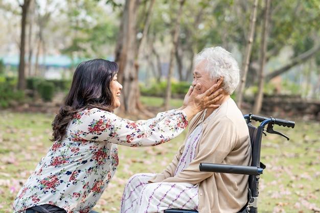 Ajuda e carro paciente asiática sênior da mulher sentada em uma cadeira de rodas no parque.