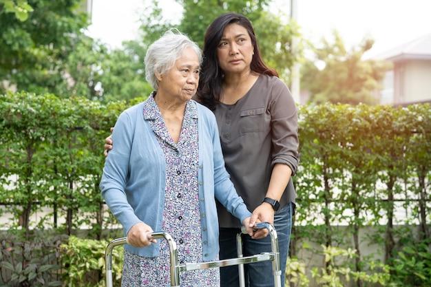 Ajuda e cuidado mulher idosa asiática sênior ou idosa usar o andador com saúde forte enquanto caminhava no parque em um feriado fresco e feliz.