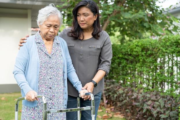 Ajuda e cuidado mulher idosa asiática usando andador enquanto caminha no jardim em casa