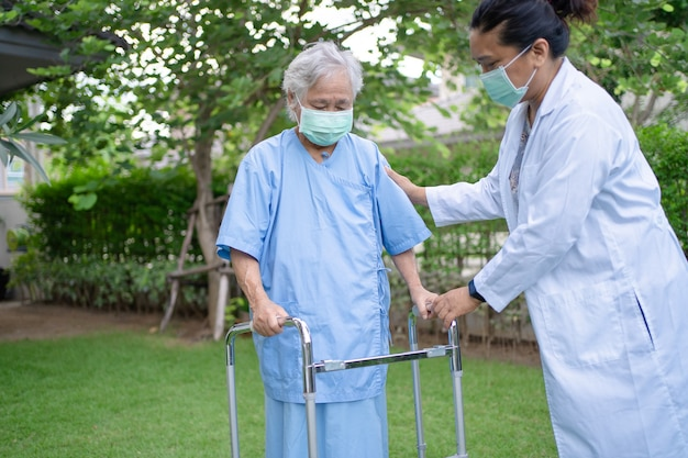 Ajuda e cuidado mulher idosa asiática usando andador enquanto caminha no parque