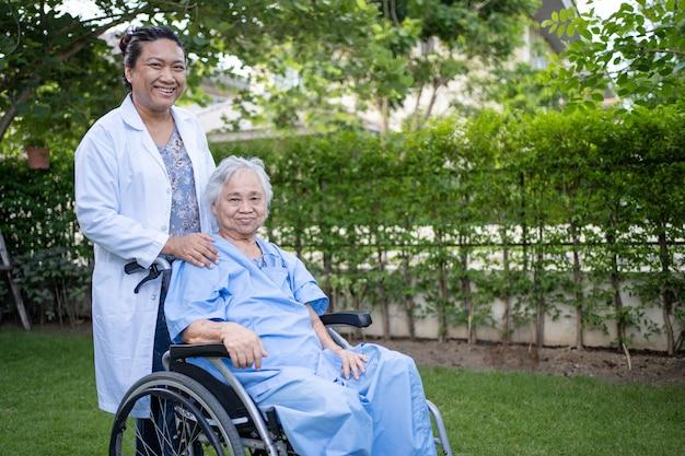Ajuda e cuidados médicos paciente asiática sênior, mulher, sentada em uma cadeira de rodas no parque