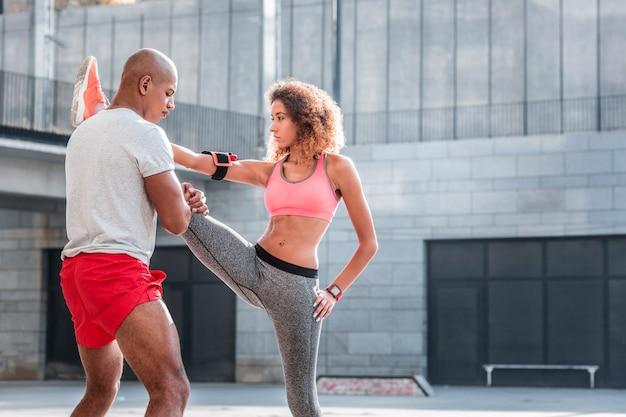 Ajuda e suporte. jovem simpático segurando a perna da namorada enquanto a ajuda a fazer o exercício