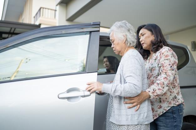 Ajuda e suporte paciente asiático sênior ou idosa senhora sentada na cadeira de rodas, prepare-se para chegar ao carro dela: saudável forte conceito médico.