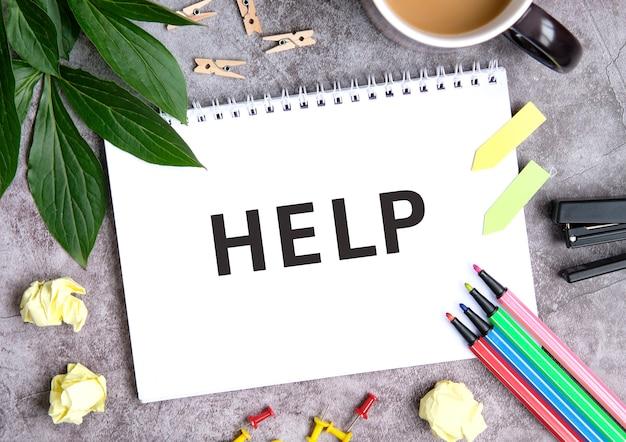 Ajuda em um caderno com uma xícara de café, folhas comprimidas, giz de cera e grampeador