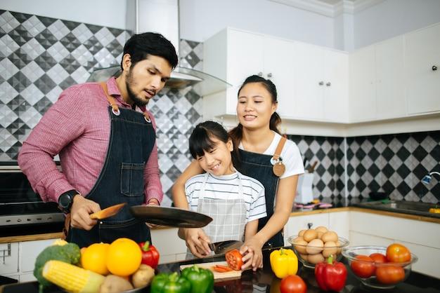 Ajuda feliz da família que cozinha a refeição junto na cozinha em casa.
