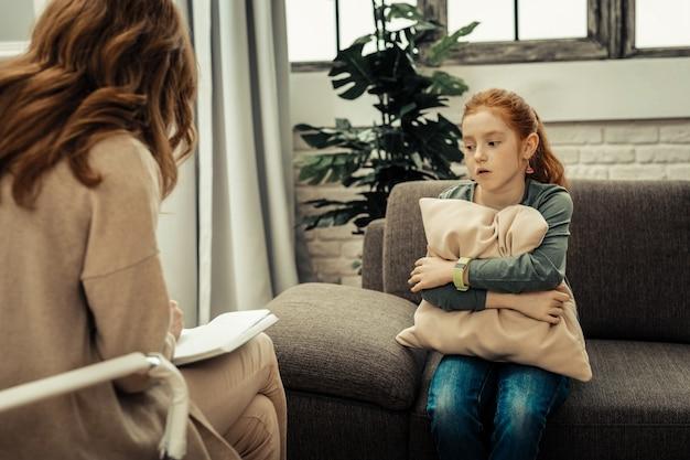 Ajuda profissional. menina melancólica e desanimada abraçando o travesseiro enquanto se submetia a um tratamento psicológico