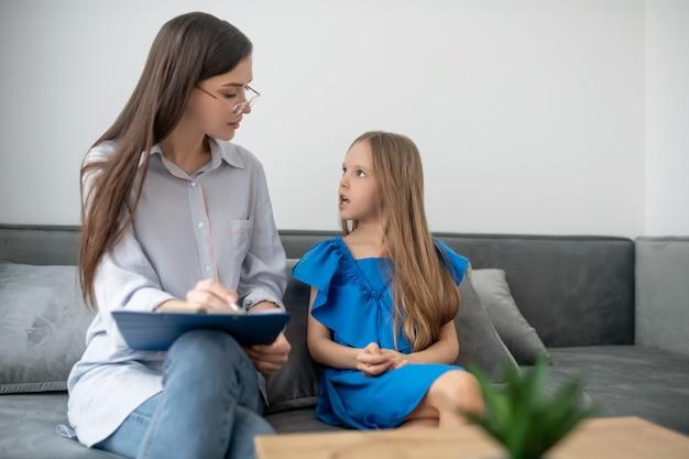 Ajuda psicológica. uma garota de vestido azul tendo uma reunião com um psicólogo