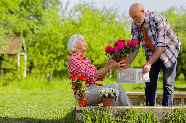 Ajudando a linda esposa. marido aposentado barbudo ajudando sua linda esposa cuidando das flores