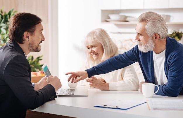 Ajudando a tomar uma decisão. consultor financeiro profissional confiante e hábil, conversando com clientes idosos e usando laptop enquanto expressa positividade