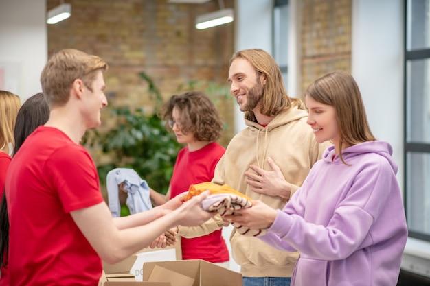 Ajudando, necessitado. jovens voluntários sorridentes distribuindo ajuda aos necessitados em instalações de centros de caridade