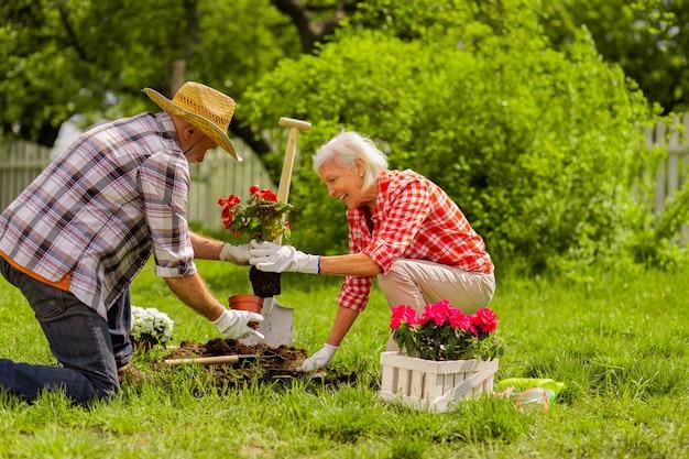 Ajudando no plantio. marido amoroso aposentado com chapéu de palha ajudando a esposa a plantar flores
