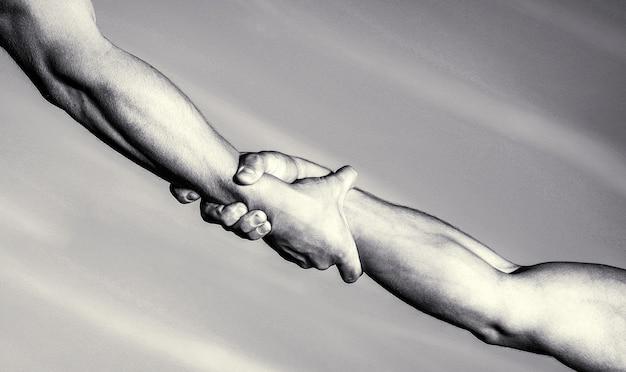 Ajudando o conceito de mãos, suporte. conceito de mão amiga e dia internacional da paz, apoio. duas mãos, ajudando o braço de um amigo, trabalho em equipe. mãos no fundo do céu azul. preto e branco.