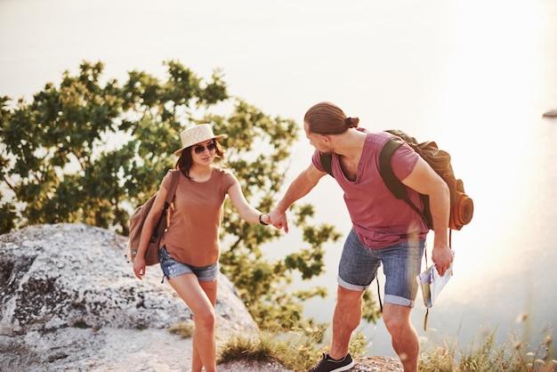 Ajudando. o jovem casal decidiu passar as férias de forma ativa na beira de uma linda rocha com um lago ao fundo.