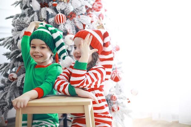 Ajudantes do papai noel. crianças fofas em fantasias de duende do natal em uma sala lindamente decorada para o natal. tempo de milagres. presentes do papai noel.