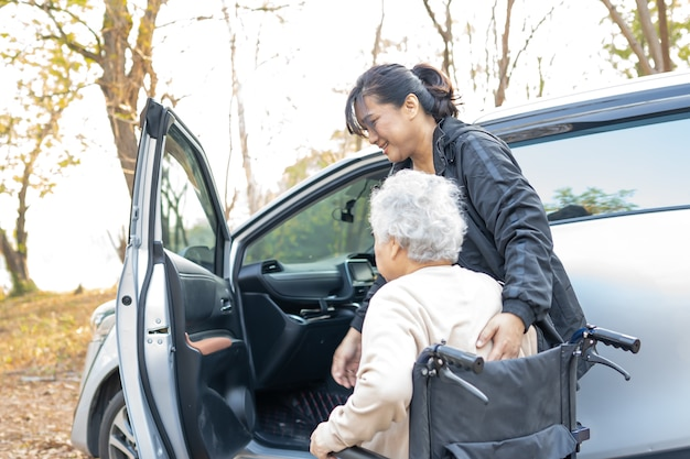 Ajudar e apoiar a mulher asiática sênior sentada em uma cadeira de rodas no carro.
